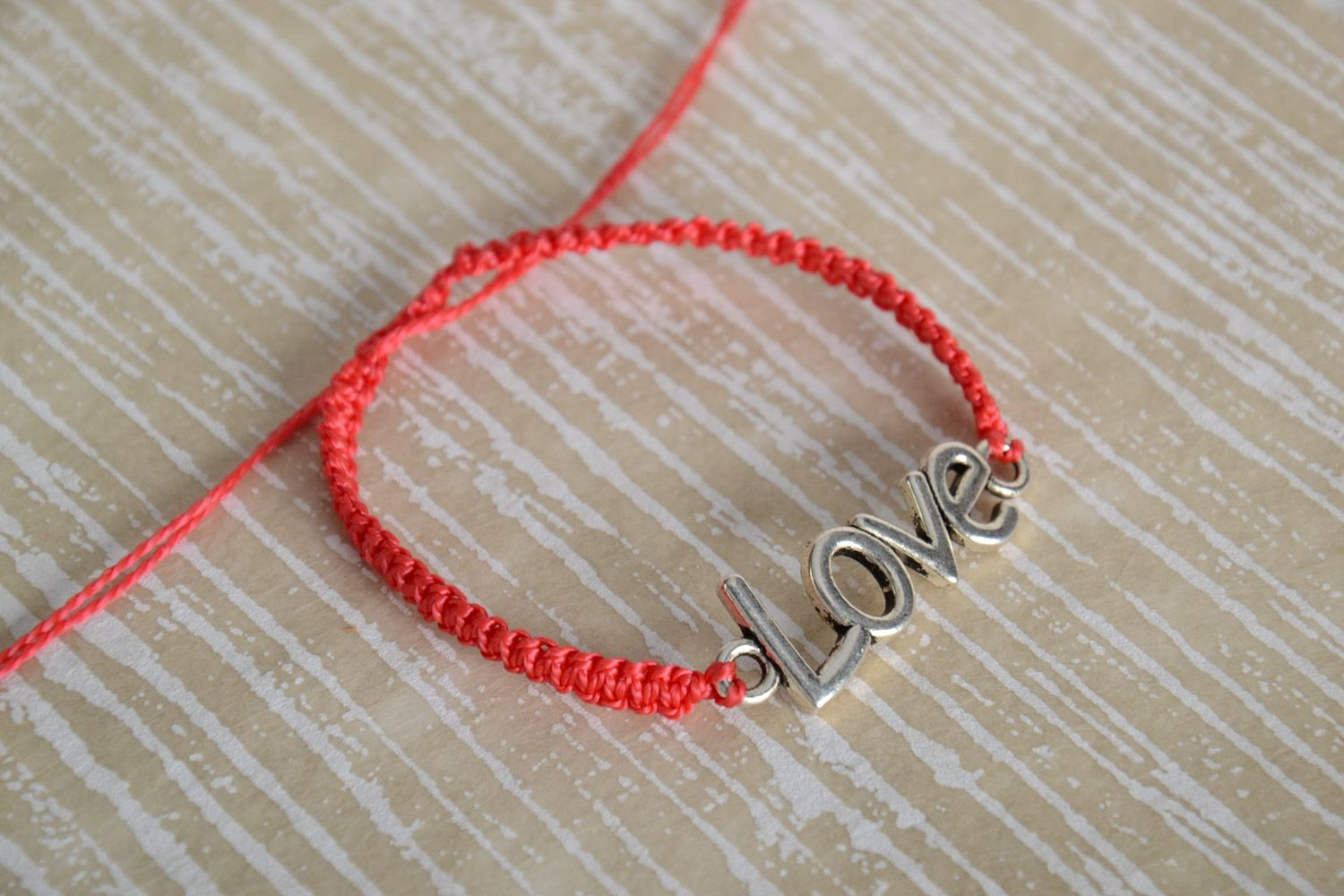 Handmade women's woven cord bracelet of red color with metal charm lettering photo 1