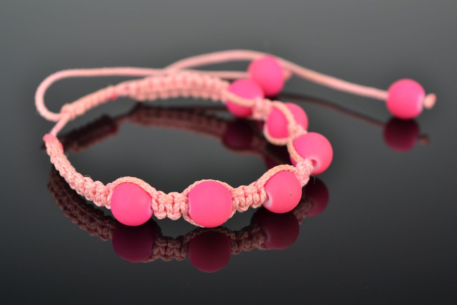 Woven bracelet with pink plastic beads photo 1