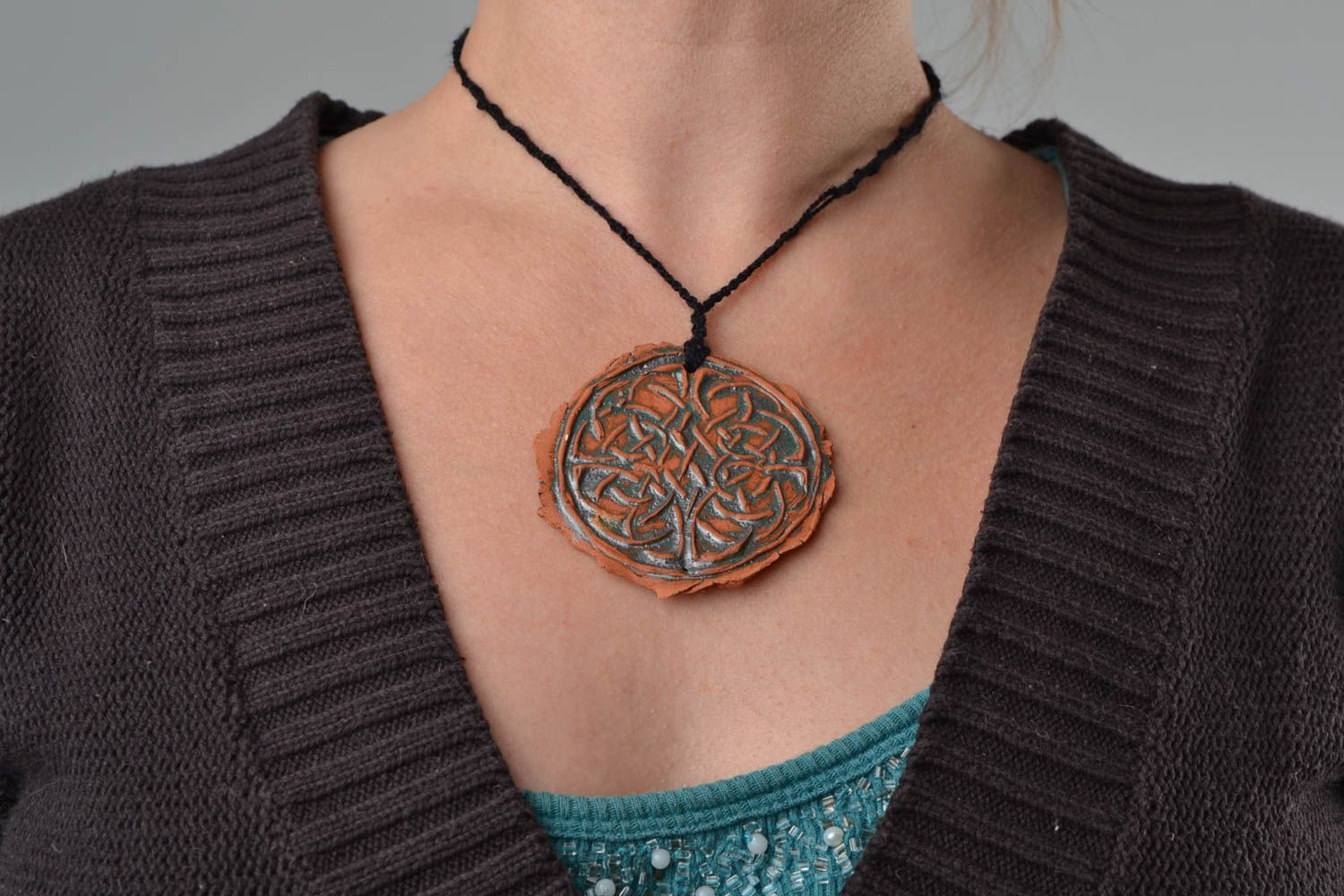 Handmade women's designer ceramic round pendant with relief ornament on cord photo 2
