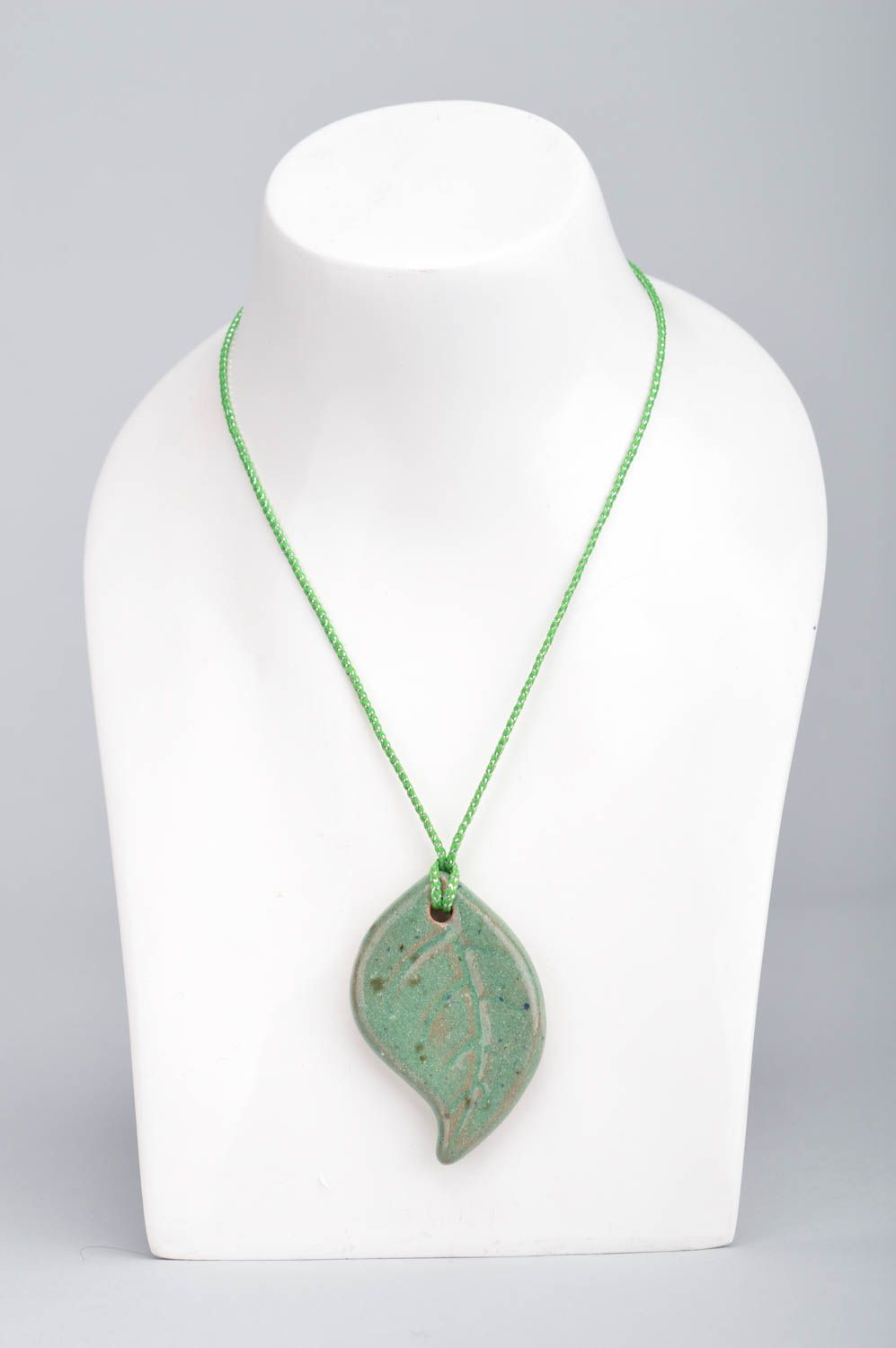 Handmade ceramic small pendant in the shape of light green leaf on a cord photo 5