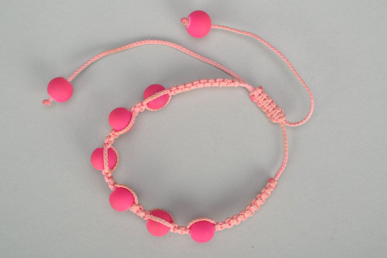 Woven bracelet with pink plastic beads photo 2