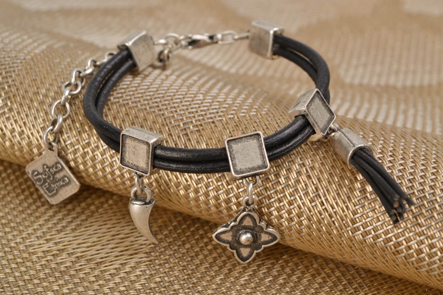 Metal bracelet with cord and charms photo 1