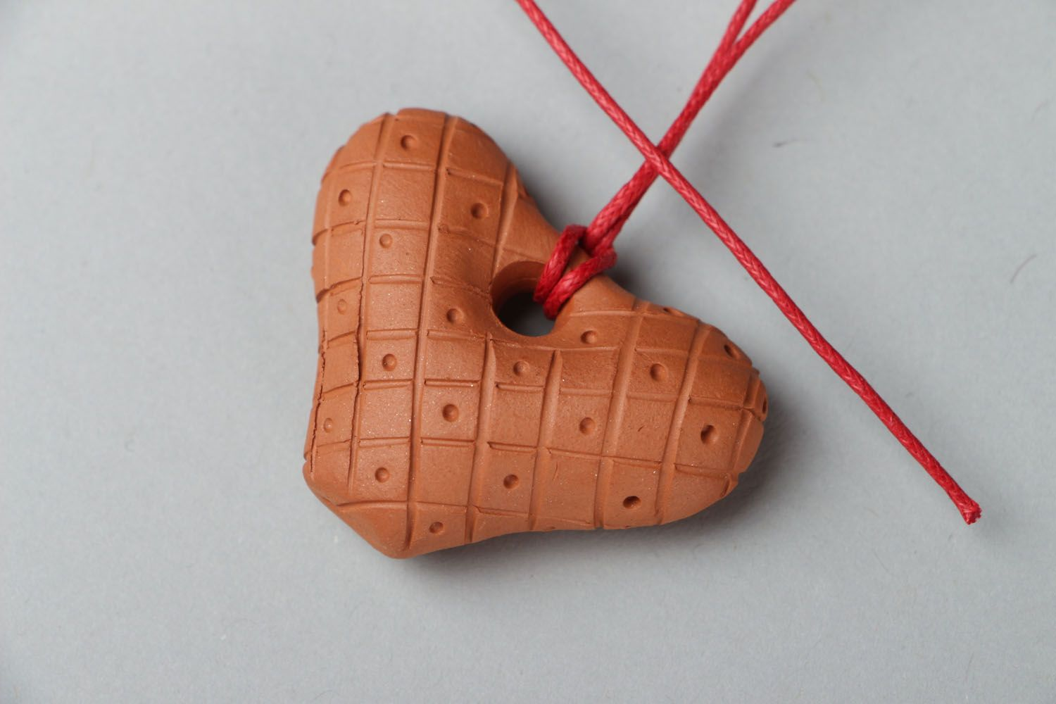 Clay penny whistle with a red cord photo 1