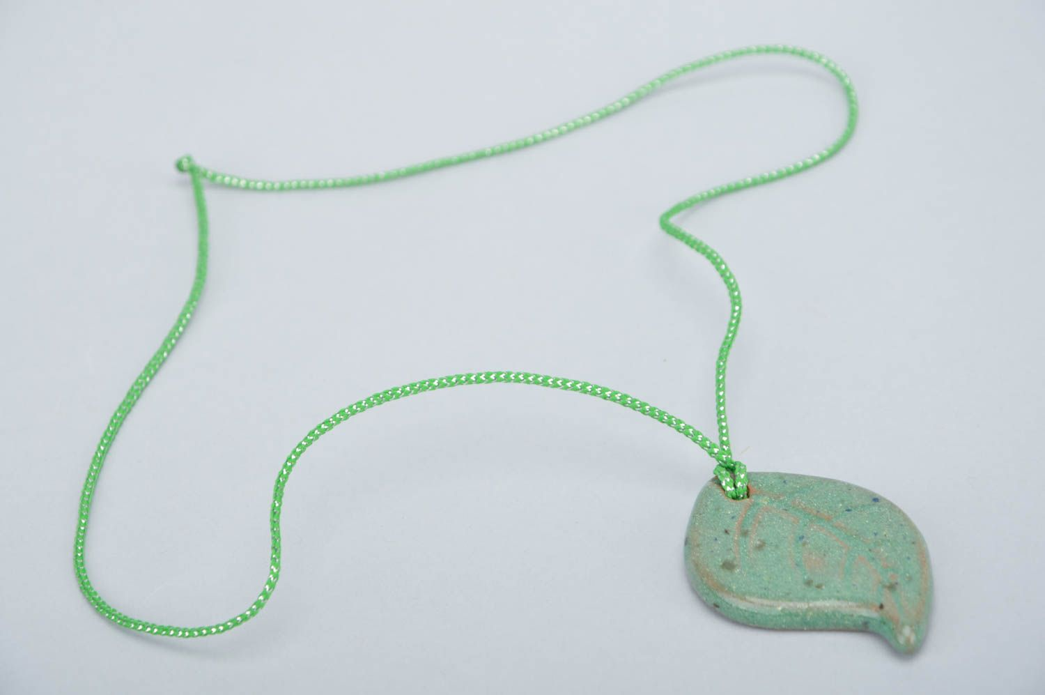 Handmade ceramic small pendant in the shape of light green leaf on a cord photo 2