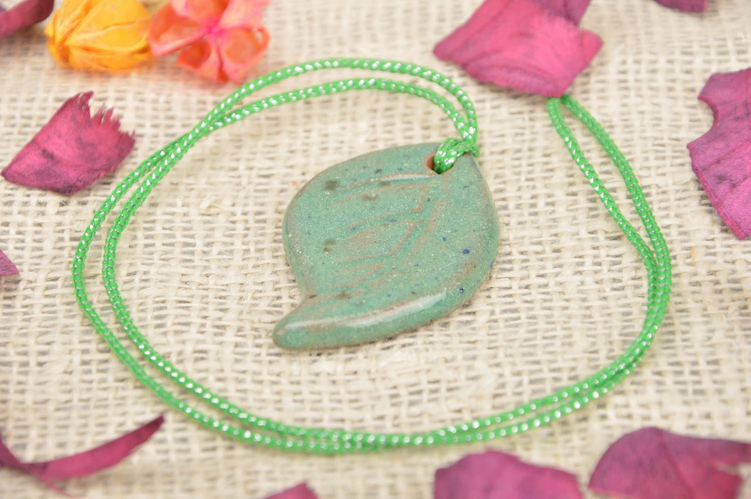 Handmade ceramic small pendant in the shape of light green leaf on a cord photo 1
