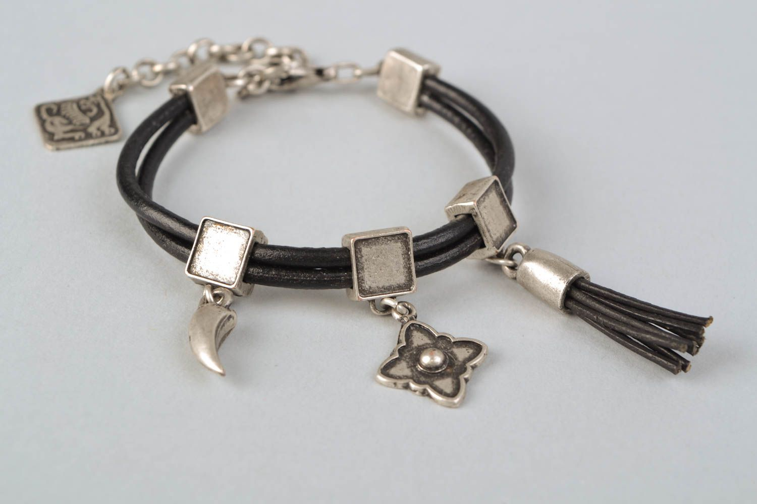 Metal bracelet with cord and charms photo 4