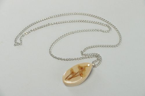 Handmade light oval pendant with flowers embedded in epoxy resin on long chain - MADEheart.com