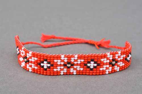 Handmade red beaded wrist bracelet with ties and white flower pattern - MADEheart.com