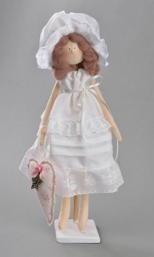 Handmade cute toy doll made of fabric in white dress and bonnet on stand - MADEheart.com